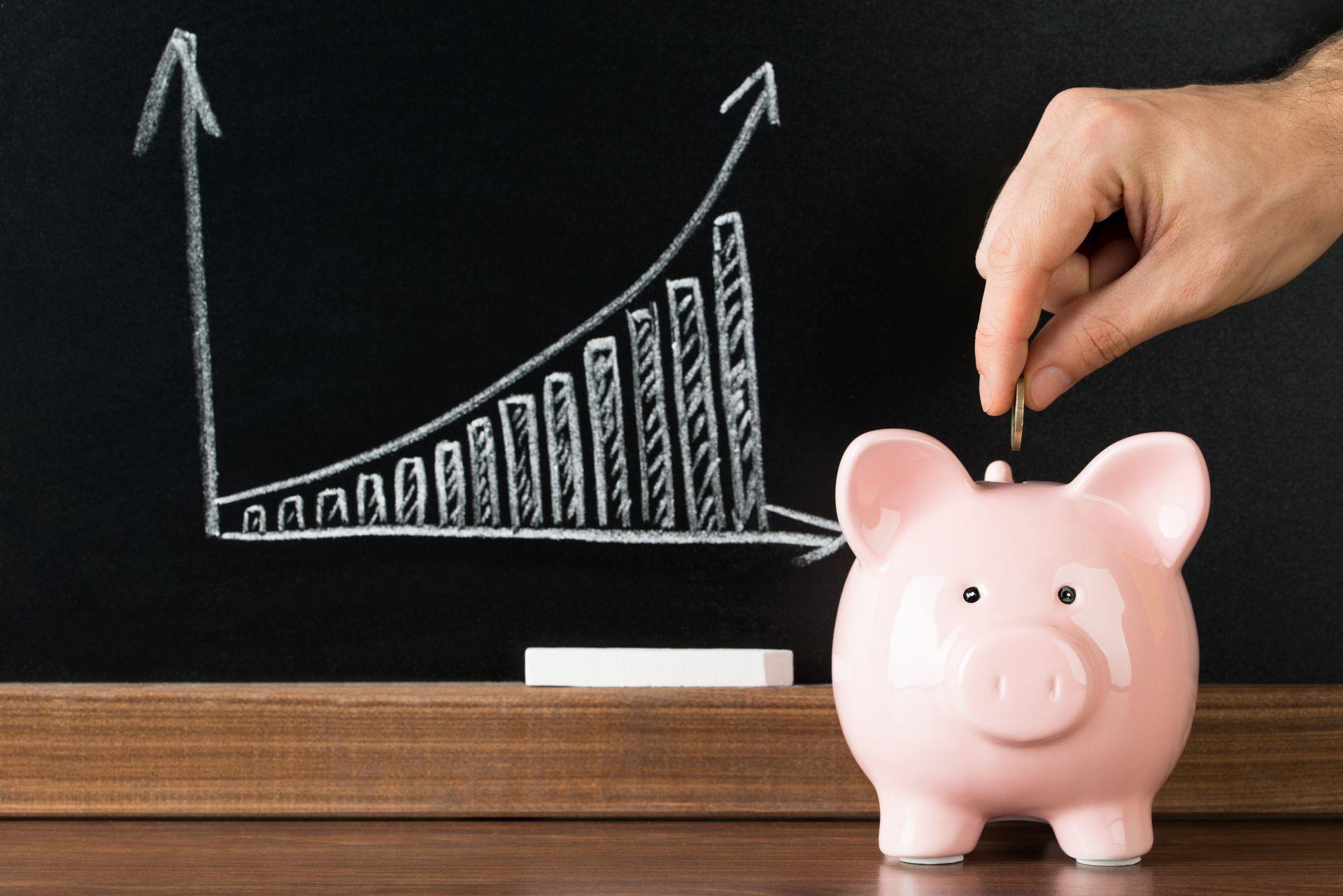 Zdjęcie przedstawia narysowane na czarnej tablicy białą kredą słupki symbolizujące wzrost, obok do różowej świnki-skarbonki ręka wrzucająca monetę
