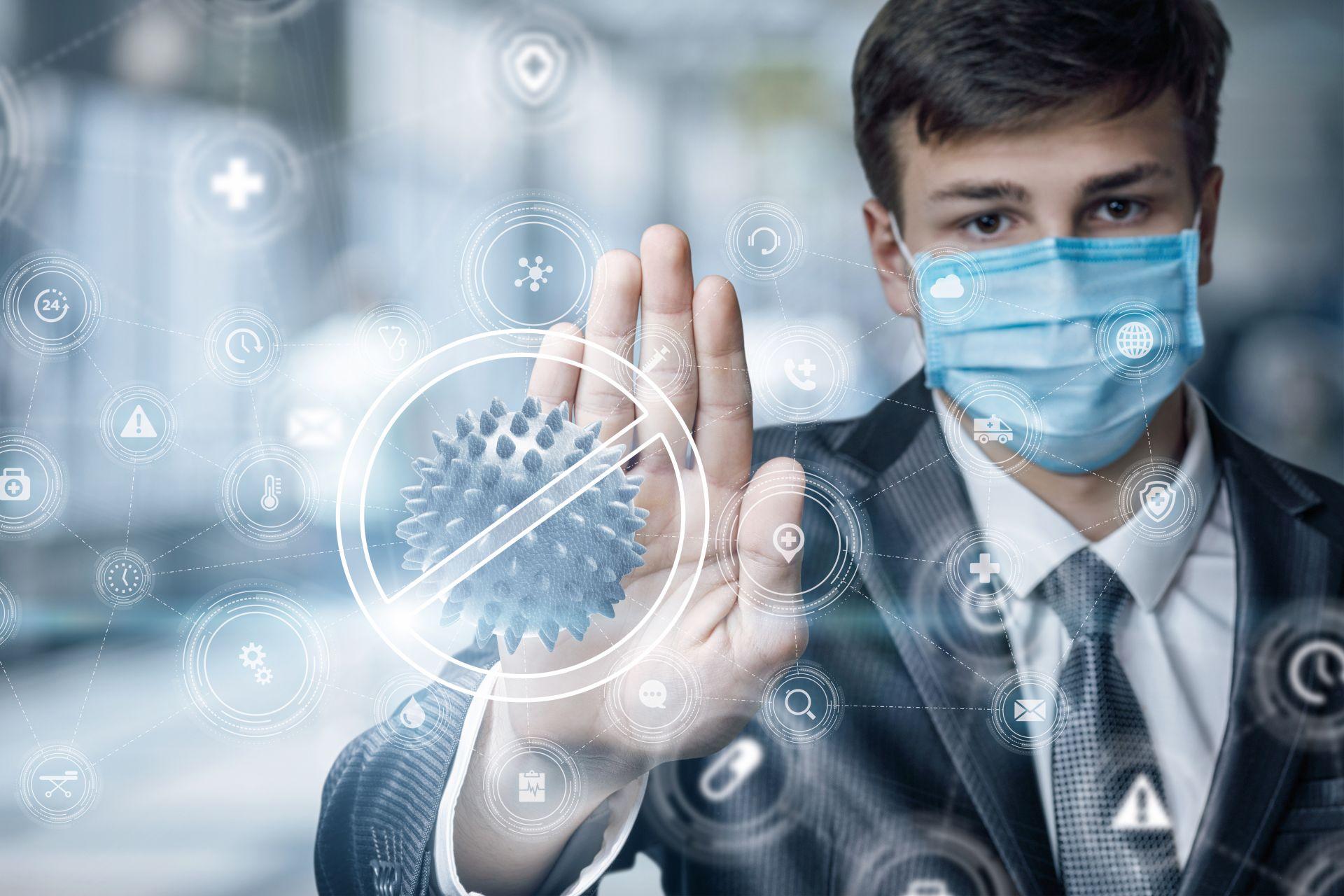 Zdjęcie przedstawia mężczyznę ubranego w garnitur , w maseczce ochronnej na twarzy, który dłonią powstrzymuje symbolicznego wirusa