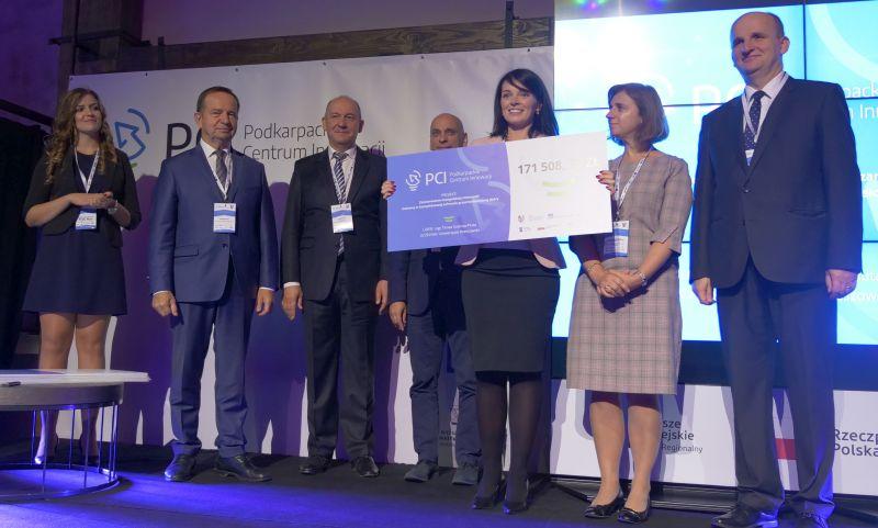 Na pierwszym planie kobieta trzymająca symboliczny papierowy czek na grant. W tle za nią stoją m.in. marszałek Władysław Ortyl i Jacek Kubrak, prezes PCI