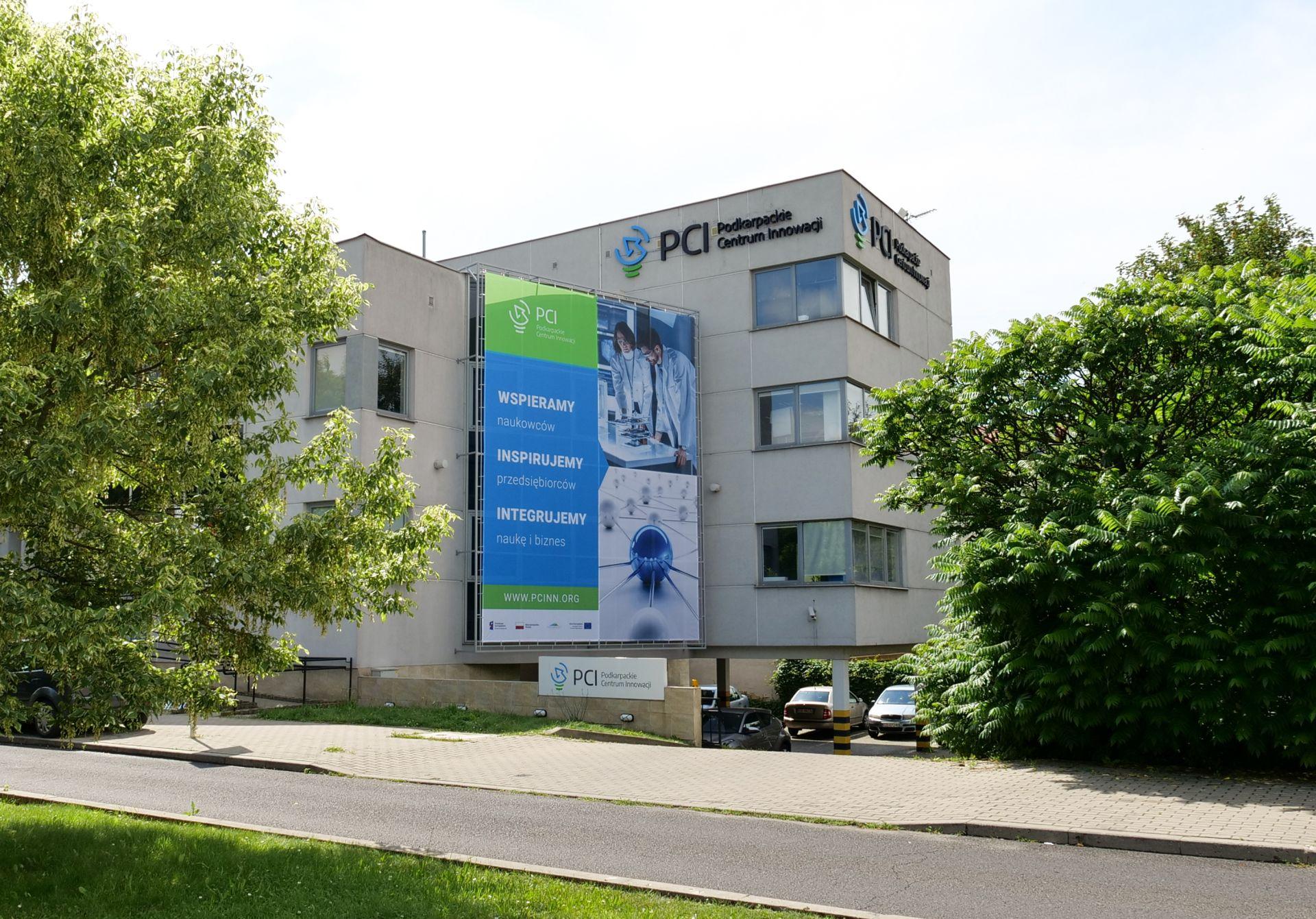 Siedziba Podkarpackiego Centrum Innowacji (PCI). Na budynku ogromny baner z napisem: Wspieramy naukowców, inspirujemy przedsiębiorców, integrujemy naukę i biznes