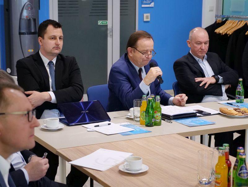 Marszałek Władysław Ortyl trzyma mikrofon w ręku. Po obu jego stronach siedzą przy stole mężczyźni ubrani w garnitury. Na stole ustawione szklanki i butelki z sokami.