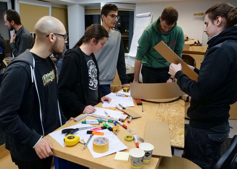Grupa pięciu mężczyzn pochylona nad stołem w pracowni ProtoLab. Na stole leżą taśmy, kolorowe mazaki i tektura
