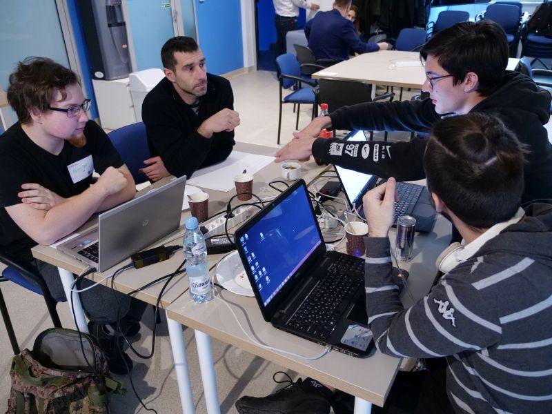 Na przeciw siebie przy stolikach siedzą z laptopami młodzi mężczyzni