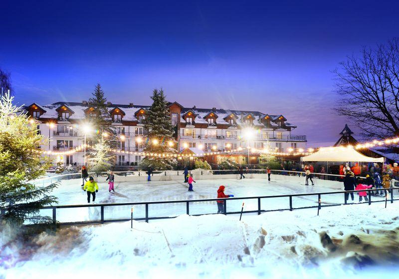 Sztuczne oświetlone lodowisko wieczorową porą, po którym jeździ na łyżwach kilka osób. W tle widoczny Hotel Skalny
