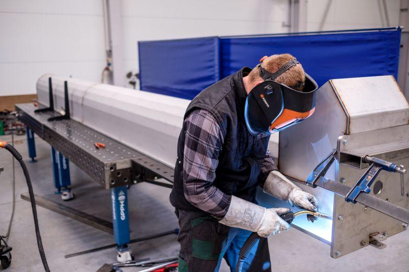 mężczyzna pracuje przy zespawaniu elementu metalowego