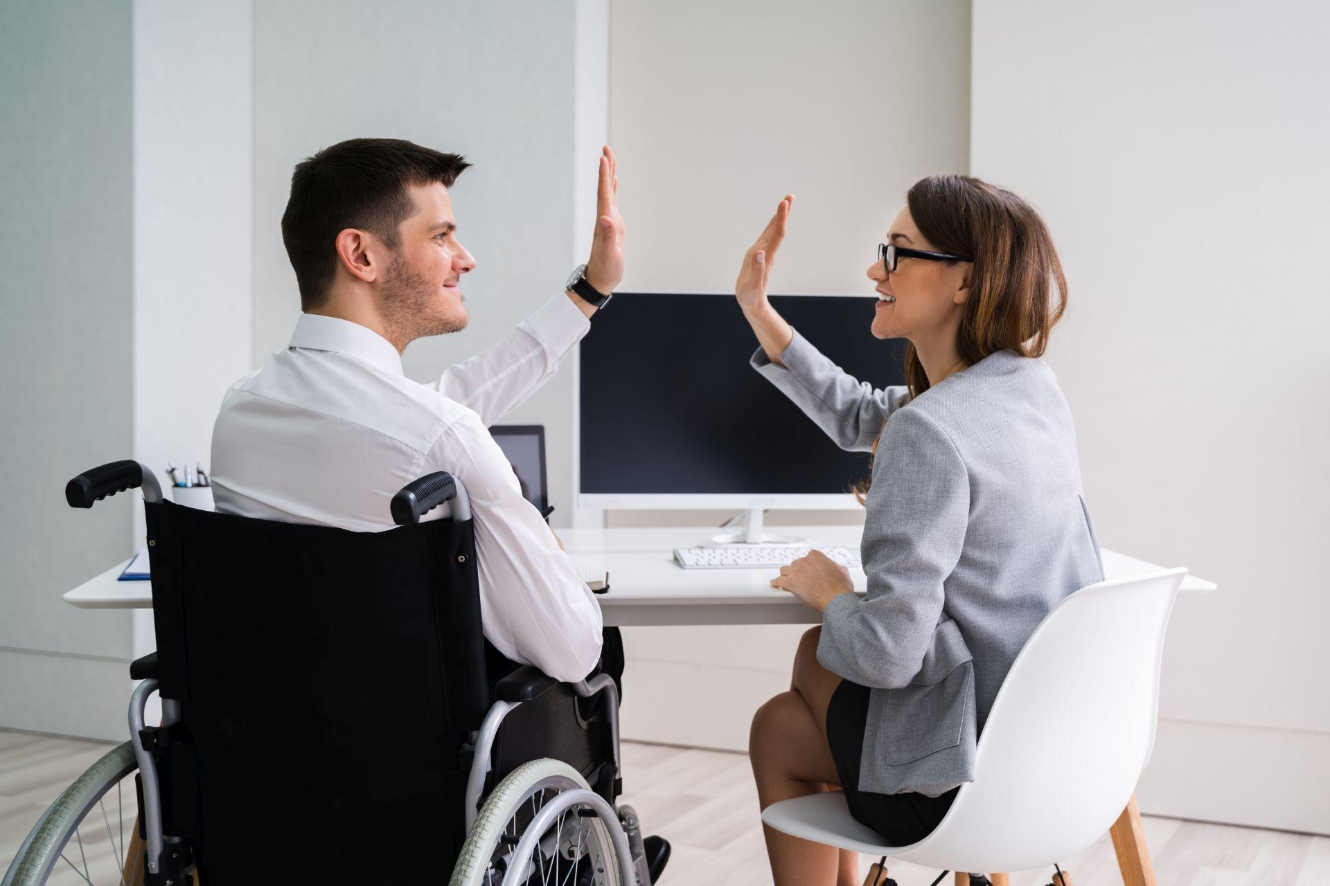 """Mężczyzna siedzący na wózku przybija """"piątkę"""" z kobietą siedzącą obok na krześle"""