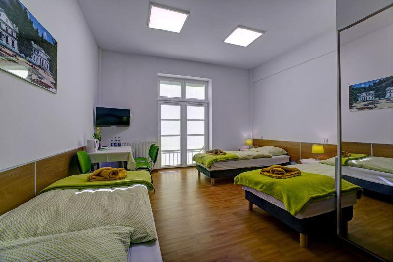 trzy łóżka i stolik w nowym pokoju