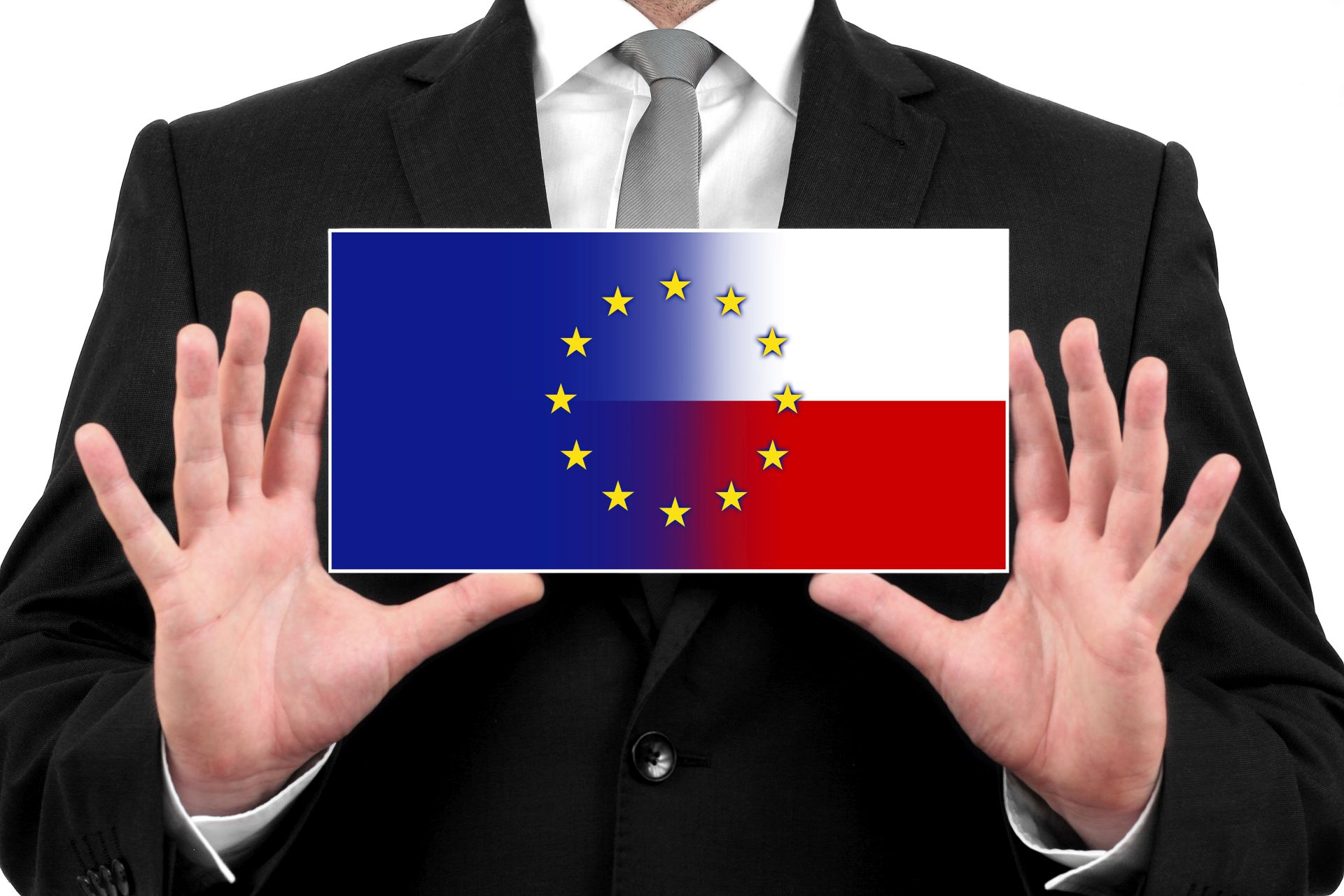 mężczyzna w garniturze trzyma w rękach obrazek, na których w połpowie jest flaga unijna i flaga Polski