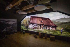 ekran mulimedialny z widokiem na wiejską chatę