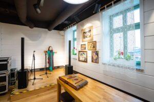 sala weselna: podium dla kapeli muzycznej i długi stół, na ścianach reprodukcje zdjęć weselnych