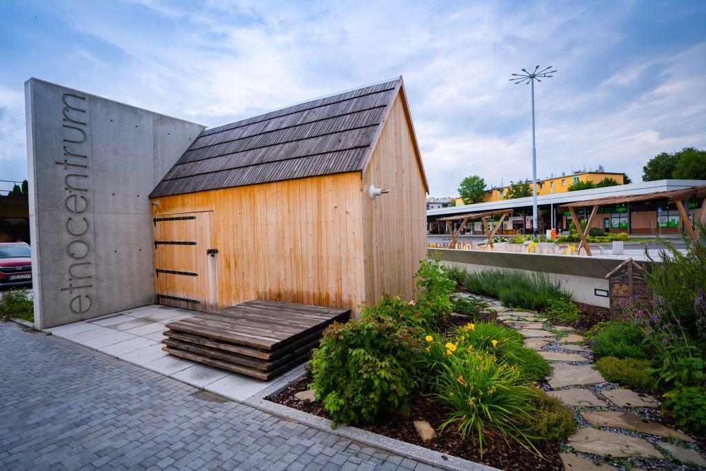 na placu przed dworcem stoi drewniana chata wiejska wraz z ogródkiem ziołowym